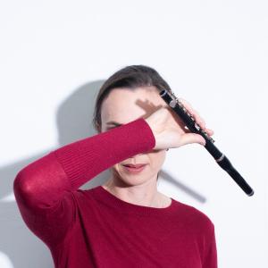 Kiri Sollis holding a piccolo across her face