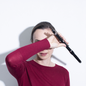 Kiri Sollis holding a piccolo. Her forearm is covering her face.