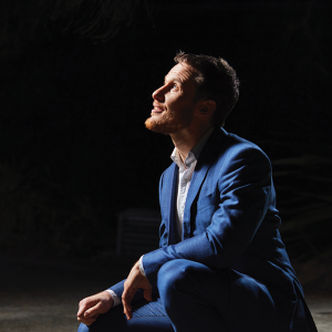 Portrait of Michael Sollis squatting and looking upwards towards a source of light.